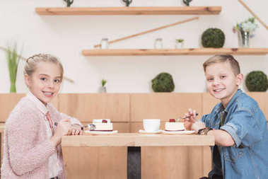 children sitting at table at cafe while looking at camera other and smiling