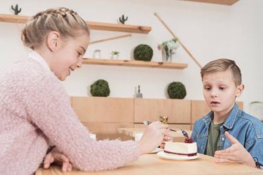 children sitting at table at cafe while looking at cake on table at cafe
