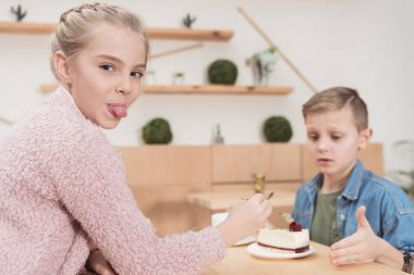 kid showing tongue to camera while sitting at table against boy in cafe