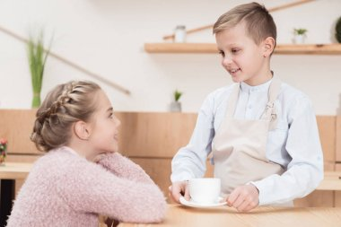 little waiter with cup in hands looking on kid sitting at table at cafe