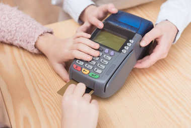 cropped view of kid paying with credit card in payment terminal