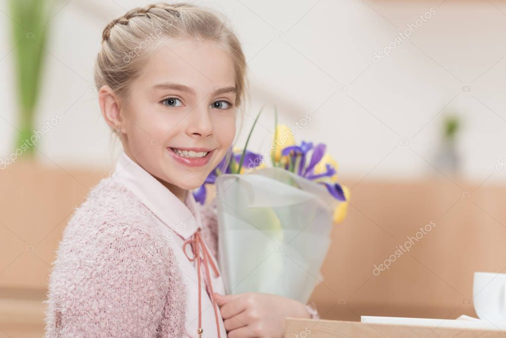 smiling kid holding bouquet of flowers in hands and looking at camera