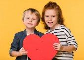 portrét dětí drží červené papírové srdce společně izolované na žluté, st valentines day koncept
