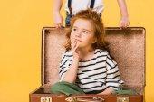 částečný pohled zasněný kluk, co v kufru s chlapcem, stojící poblíž izolované na Yellow