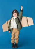 Photo cute little boy in pilot costume with paper plane wing isolated on blue