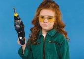 Fotografie portrét dítěte v pilotní kostým s hračka šroubovák izolovaný na modré