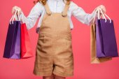 Fotografia ritagliata colpo di kid in abbigliamento casual con sacchetti di acquisto isolati sul colore rosa