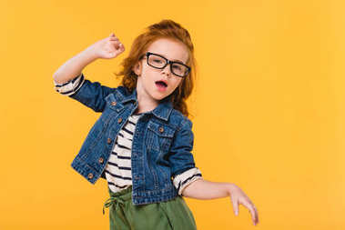 portrait of cute little kid in eyeglasses dancing isolated on yellow
