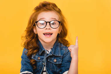 portrait of smiling little kid in eyeglasses pointing up isolated on yellow