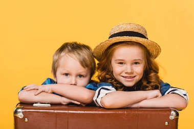 portrait of smiling kids leaning on suitcase together isolated on yellow