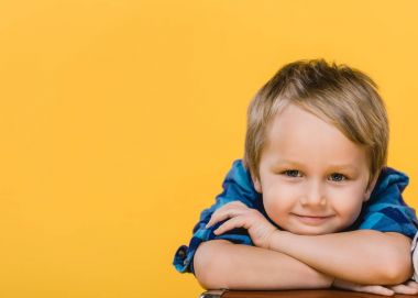 portrait of smiling little boy in shirt looking at camera isolated on yellow