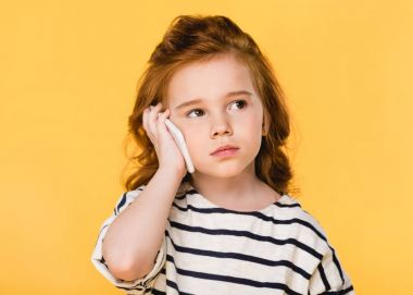portrait of cute child talking on smartphone isolated on yellow