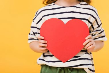partial view of kid with red paper heart in hands isolated on yellow, st valentines day concept