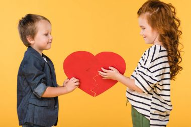 Side view of smiling kids holding red paper heart together isolated on yellow, st valentines day concept stock vector