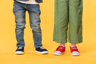 partial view of kids in casual clothing isolated on yellow