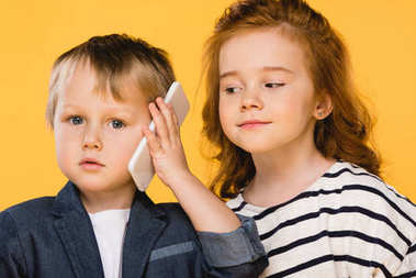 portrait of little boy talking on smartphone with friend near by isolated on yellow