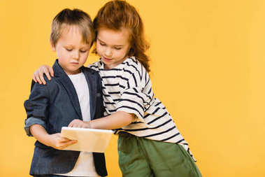 portrait of children using tablet together isolated on yellow