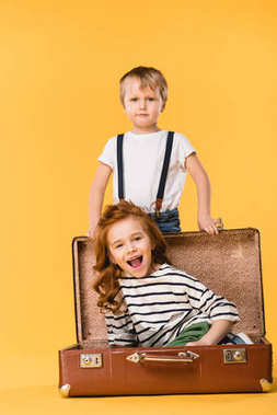 happy kid sitting in suitcase with boy standing near by isolated on yellow