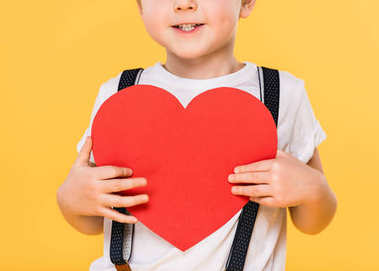 Partial view of kid with red paper heart isolated on yellow, st valentines day concept stock vector