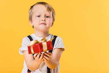 selective focus of little boy with wrapped present isolated on yellow