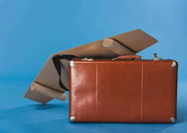 close up view of self made paper plane wings and suitcase isolated on blue