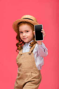 portrait of little child showing smartphone with blank screen isolated on pink