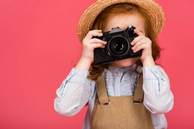 Obscured view of child holding photo camera isolated on pink stock vector