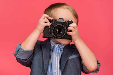 Obscured view of kid holding photo camera isolated on pink stock vector
