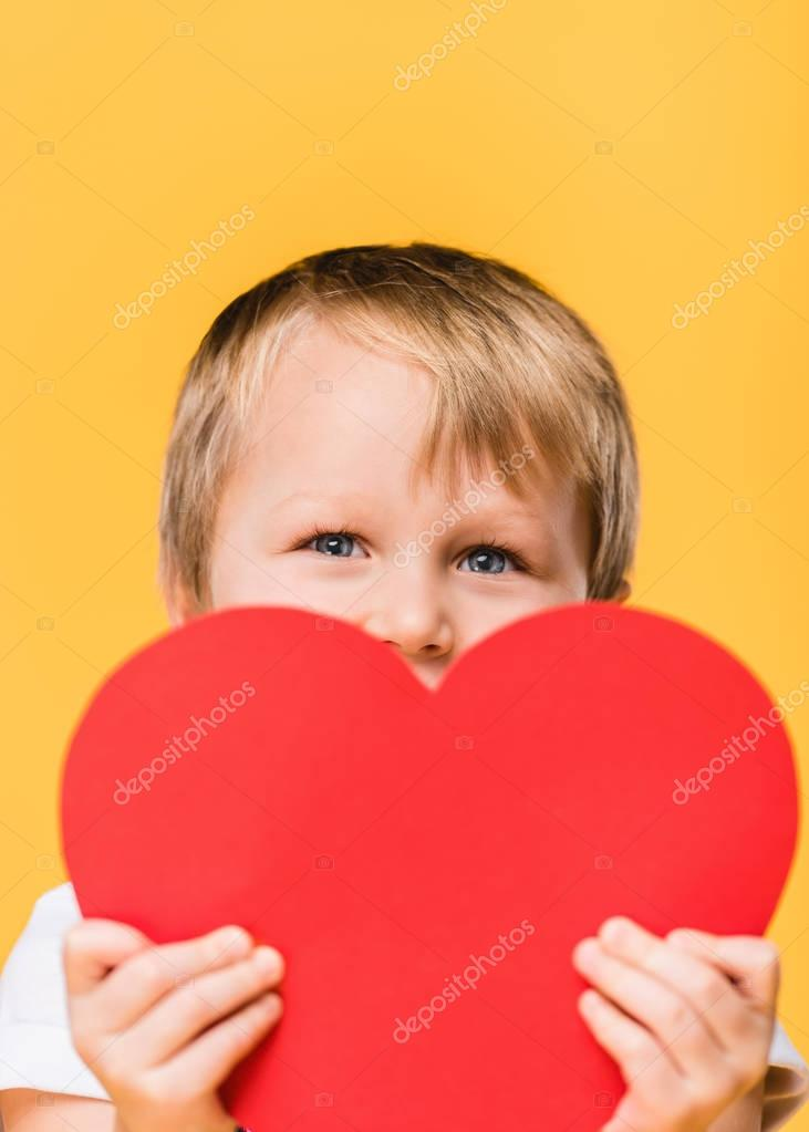 obscured view of boy covering face with red paper heart isolated on yellow, st valentines day concept