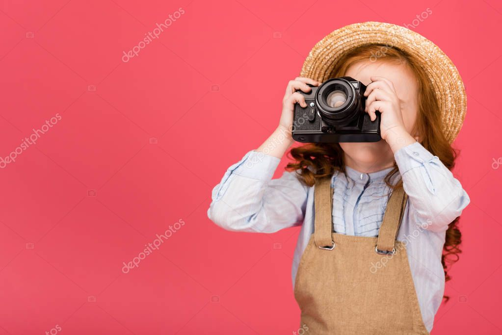 obscured view of child holding photo camera isolated on pink