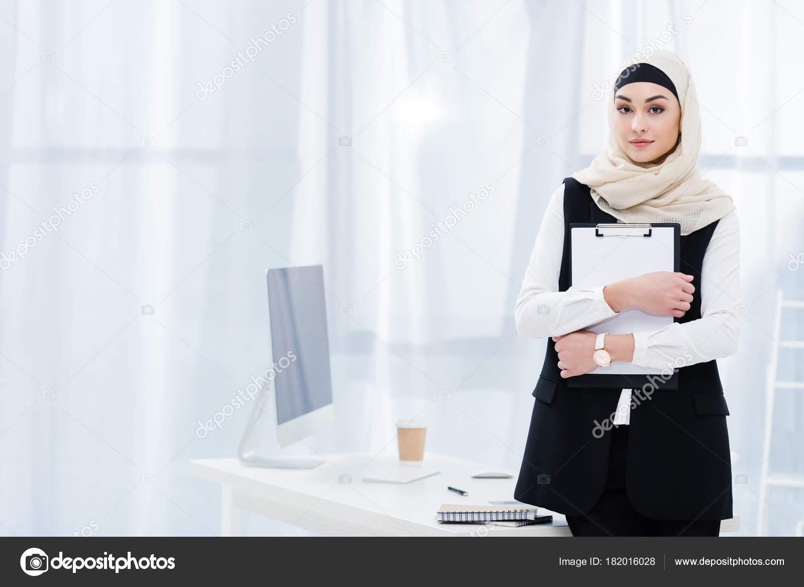 Portrait femme affaires arabe avec dossier mains bureau
