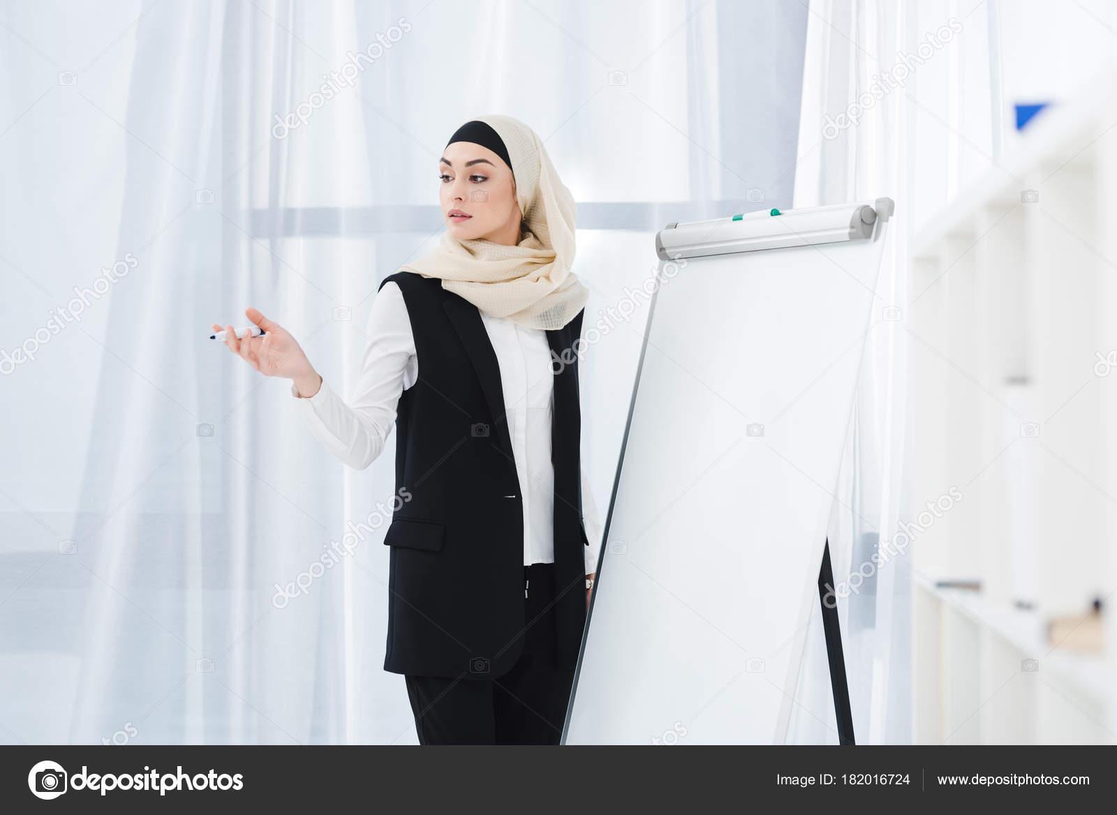 Femme arabe vêtements hijab debout tableau blanc bureau