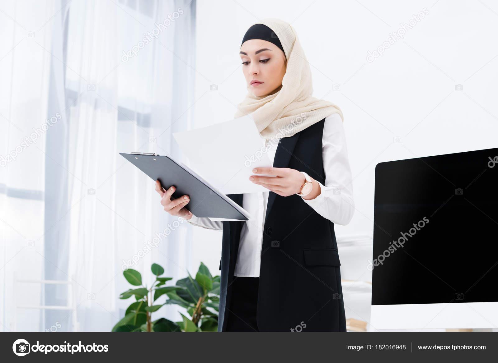 Portrait concentré femme arabe faire paperasse bureau