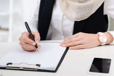 partial view of businesswoman signing papers at workplace