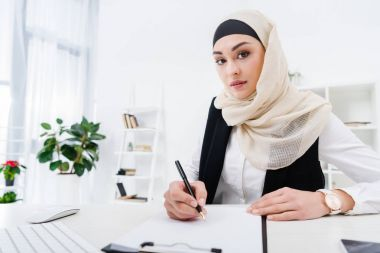 portrait of arabic businesswoman looking at camera while signing papers at workplace