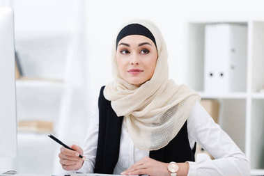 Portrait of attractive businesswoman in hijab with pen in hand at workplace in office stock vector