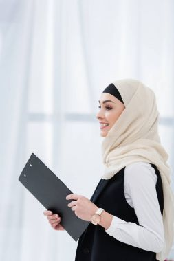 side view of smiling arabic businesswoman with folder in hands in office