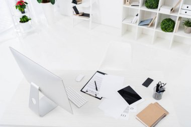 high angle view of computer screen, digital devices, contract and notebooks on table in office