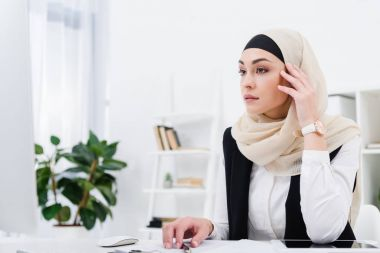 pensive arabic businesswoman sitting at workplace in office
