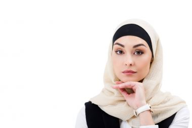 portrait of attractive arabic businesswoman in hijab looking at camera isolated on white