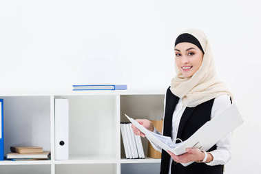 portrait of smiling businesswoman in hijab with folder in office