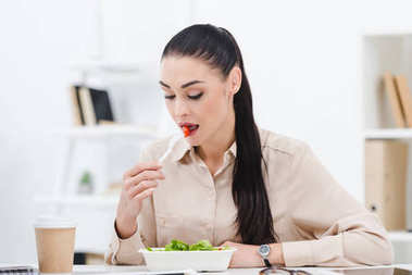 portrait of businesswoman eating take away salad for lunch in office