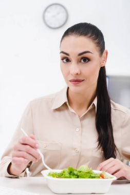 portrait of businesswoman with take away food at workplace in office