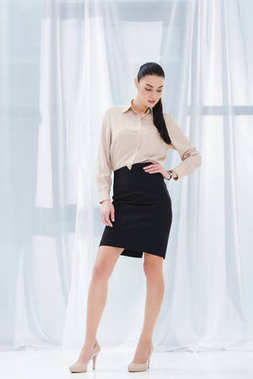 attractive and stylish businesswoman akimbo in formal wear in office