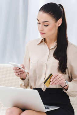 focused businesswoman with credit card and smartphone making online payment