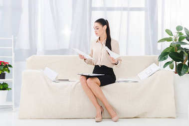 businesswoman doing paperwork while sitting on sofa in office