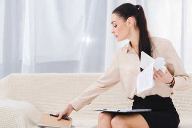 portrait of businesswoman doing paperwork while sitting on sofa in office