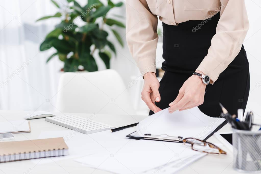 cropped shot of businesswoman doing paperwork at workplace in office