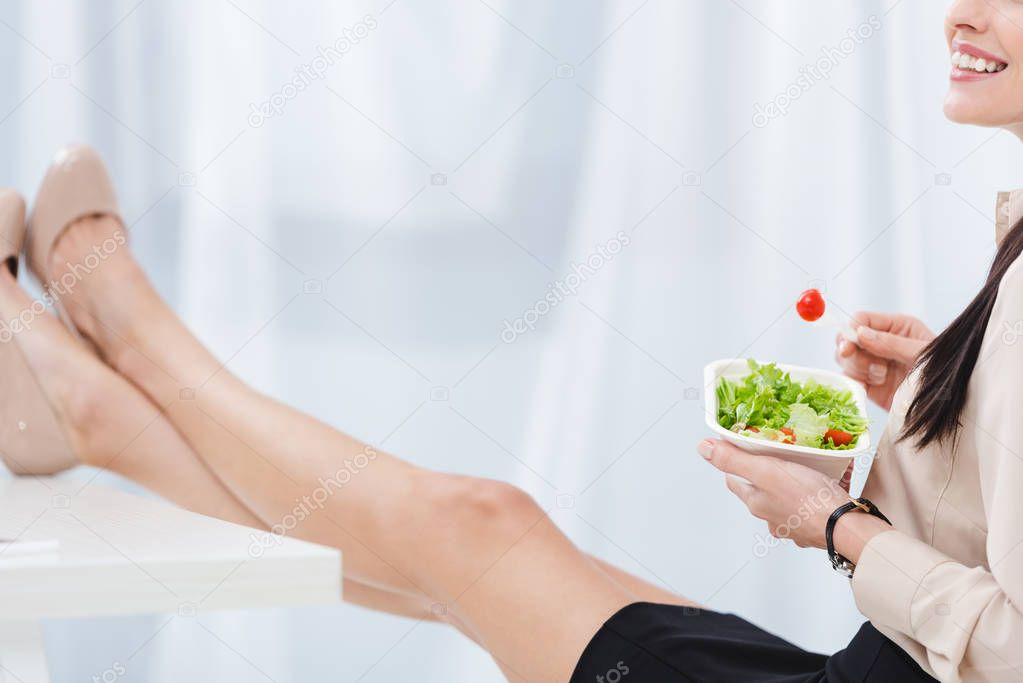 partial view of businesswoman with take away food at workplace in office