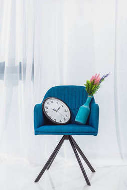Vase and clock in blue modern chair in room in front of window